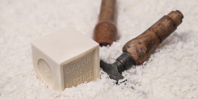 Cube de Savon de Marseille de 600g sur copeaux et entouré de tampons à savon