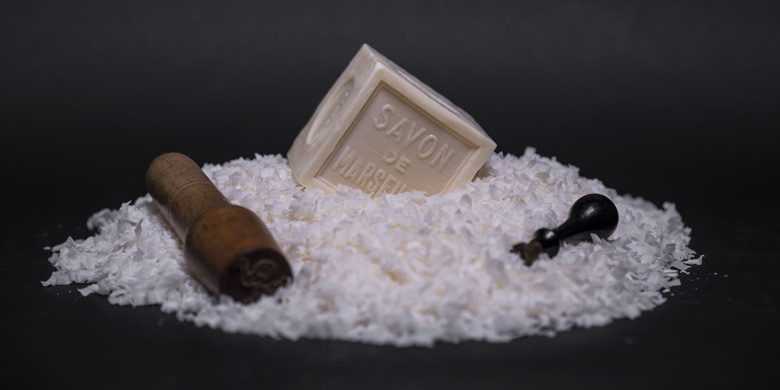 Cube de Savon de Marseille de 600g sur copeaux et entouré de tampons à savon sur fond noir
