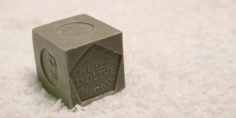 Cube de savon de Marseille à l'huile d'olive, dont il prend la couleur olive verte, produit par la Savonnerie du Midi et posé sur tapis de copeaux de savon